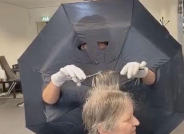 Peluquera hace agujeros en paraguas para brazos y ojos como barrera ante clientes